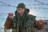 A woman in winter clothes of a prison or military type is holding her hands over the barbed wire and looks out across the barbed wire. Perhaps a female prisoner or a soldier or a hostage. Hopelesness - 242236034