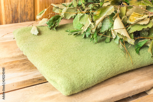 Birch broom lies on a green towel in a bath - 242243461