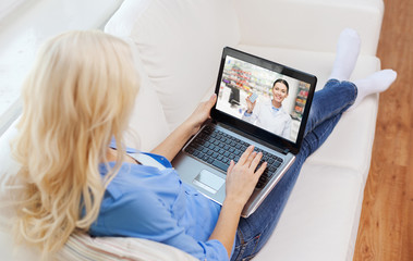 medicine, technology and healthcare concept - woman or customer having video chat with pharmacist on laptop computer at home