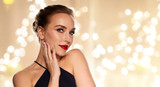 people, luxury and beauty concept - beautiful woman in black with red lipstick over beige background and festive lights - 242252050