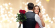 Leinwanddruck Bild - love, couple, proposal and people concept - happy woman with engagement ring and bunch of roses hugging man over beige background with festive lights