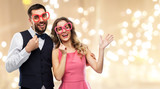 Fototapeta Panele - photo booth, fun and people concept - happy couple posing with party props over festive lights background © Syda Productions