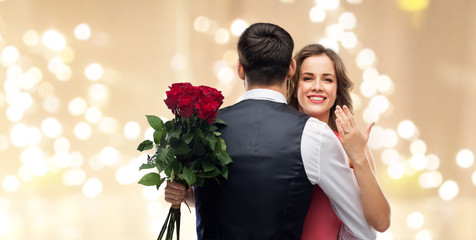 love, couple, proposal and people concept - happy woman with engagement ring and bunch of roses hugging man over beige background with festive lights
