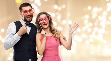 photo booth, fun and people concept - happy couple posing with party props over festive lights background