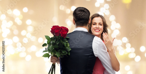 Leinwanddruck Bild love, couple, proposal and people concept - happy woman with engagement ring and bunch of roses hugging man over beige background with festive lights