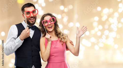 photo booth, fun and people concept - happy couple posing with party props over festive lights background - 242253085