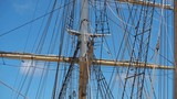Tall ship rigging gently swaying, frontlit against a blue sky and few clouds. Static shot - 242254489