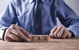 Businessman holding wooden cube with Tax word. - 242257014