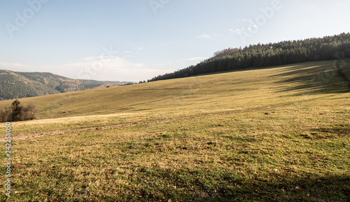 meadow with smaller hills around during nice autumn day with blue sky