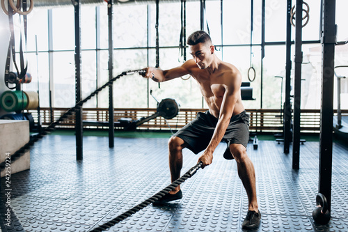 Young athletic man with a naked torso dressed in the black shorts doing sport exercises with sports ropes in the gym
