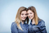 Two happy women friends wearing jeans outfit - 242260446