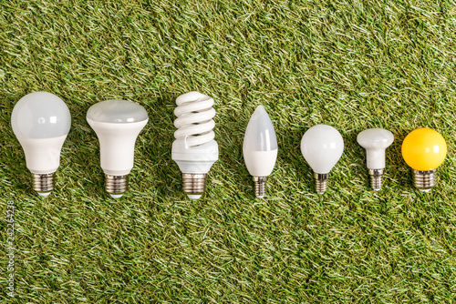 flat lay of fluorescent lamps on green grass, energy efficiency concept