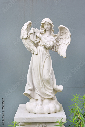 Beautiful angel statue against gray wall background. - 242266227