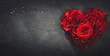 Heart-shaped red roses on stone background.
