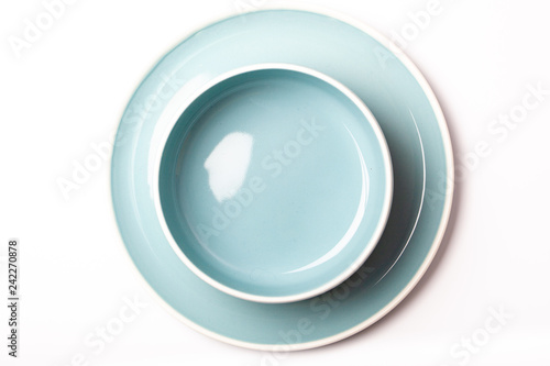 Empty pastel blue plate and bowl on white background