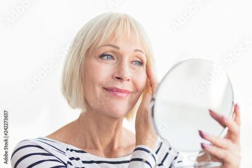Leinwanddruck Bild Senior woman touching her soft face skin