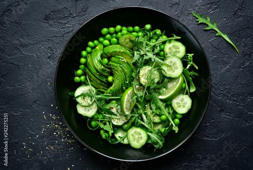 Leinwanddruck Bild Green vegetables salad (sweet pea, avocado, arugula, cucumber).Top view.