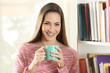 Leinwanddruck Bild - Happy woman holding a coffee cup looks at camera
