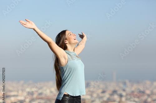 Leinwanddruck Bild Excited woman raising arms celebrating vacation