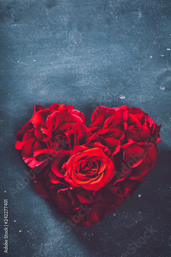 Heart-shaped rose bouquet on grey background.