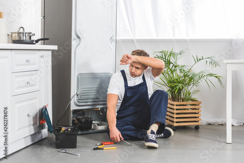 tired adult repairman sitting on floor with hand on forehead and looking at tools while repairing refrigerator