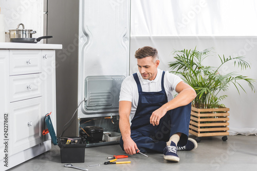 tired adult repairman sitting on floor and looking at tools while repairing refrigerator