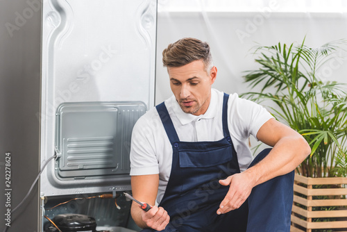 confused adult repairman looking at screwdriver while repairing refrigerator