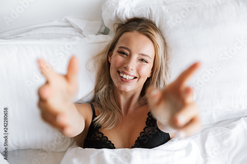 Leinwanddruck Bild Beautiful young woman in lingerie underwear lies in bed at home raises hands to camera.