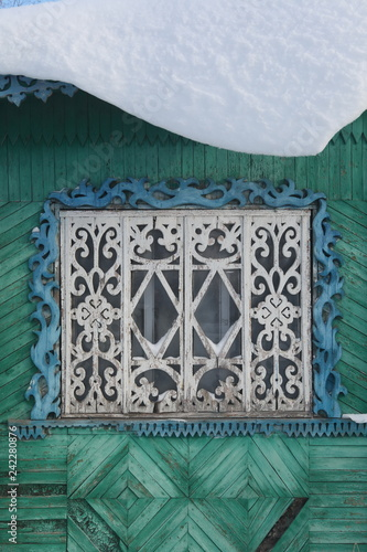 Window with carved frames on wooden house in Russian village - 242280876