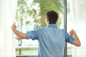 Back view of man opening curtains and looking away