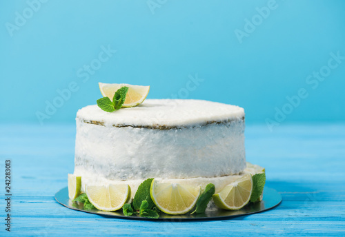 white cake decorated with lime slices on table isolated on blue