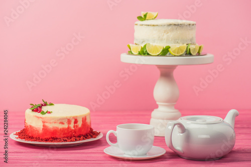 cakes decorated with currants, mint leaves and lime slices near cup and tea pot isolated on pink