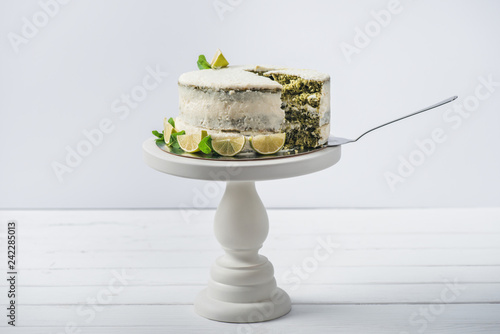 white cake decorated with mint leaves and line slices on stand isolated on white