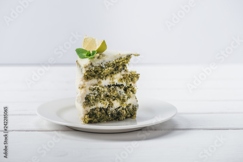 piece of white cake decorated with mint leaves and line slices on saucer isolated on white
