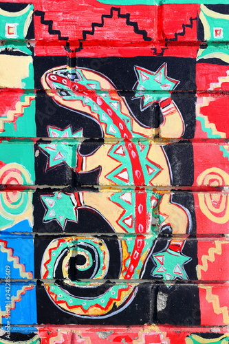 Fragment of graffiti drawings. The old wall decorated with paint lizards in the style of street art culture. Colored background texture
