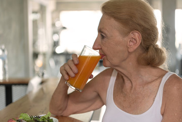 Senior woman eating healthy salad and orange juice. elderly health lifestyle concept. © barameefotolia