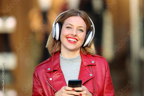 Fashion girl listening to music from phone looking at you - 242289672