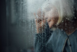 blurred portrait of lonely senior woman at home through window with raindrops - 242289812