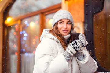Outdoors lifestyle fashion portrait of stunning girl walking on the holiday city. Smiling, drinking coffee and enjoying life. Wearing stylish coat, gray hat. Festive mood