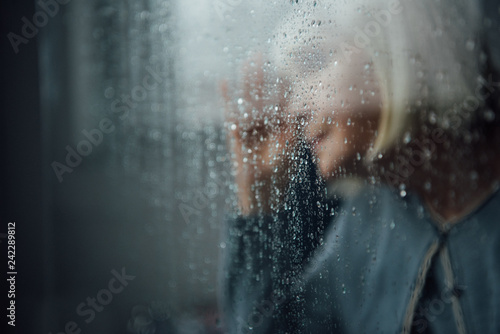 Leinwanddruck Bild blurred portrait of lonely senior woman at home through window with raindrops