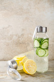 Organic summer cold refreshing drink, detox infused water, with lemon fruit and cucumber vegetables. Vegan lifestyle, weight loss and fitness. On a light wooden background, copy space