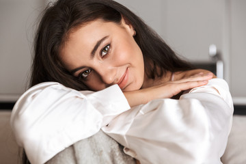 Image of beautiful woman 30s wrapped in blanket smiling, and sitting on couch in apartment
