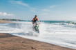 Young afro american woman riding enduro motorbike on the beach splashing the water