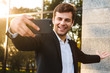 Photo of smiling office worker in suit holding mobile phone for selfie, while standing outdoor against building