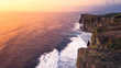 Quadro The guy on the cliff of Uluwatu over the ocean at sunset Bali Indonesia