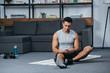 Leinwanddruck Bild - bi-racial man holding smartphone and listening music in earphones on fitness mat