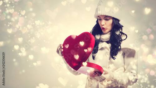 Leinwandbild Motiv Happy young woman holding a big heart gift box