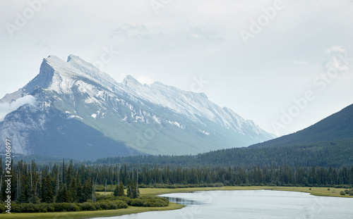 Leinwanddruck Bild River Running Through Wooded Valley Between Mountains In Alaska