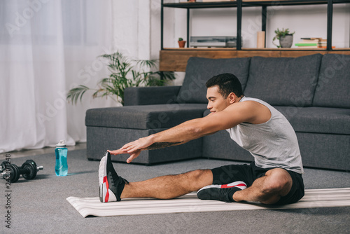 Poster mixed race man doing stretching exercise on fitness mat in living room