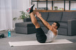 strong mixed race man doing exercise on fitness mat in living room